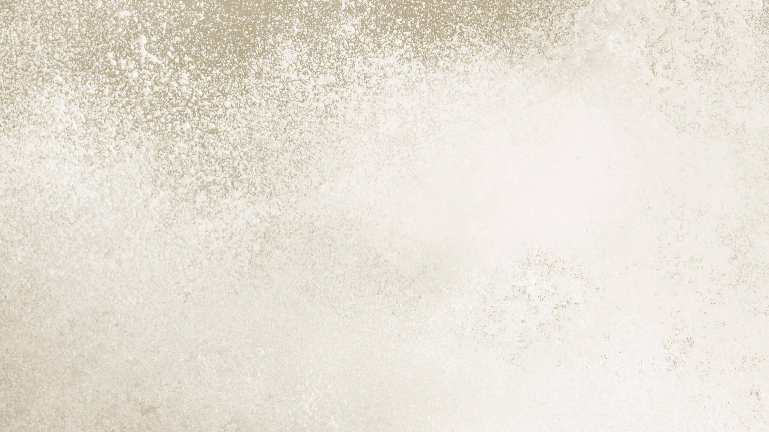 Behind Vanilla Bean flavor powder, a flurry of bright white snow is pictured.